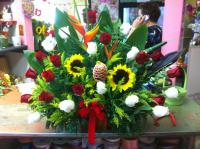 this is an tropical arrangement it consists of sun flowers and rosas
