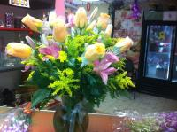 yellow roses in a vase with mixed flowers
