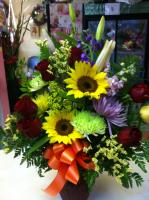 a vase arrangement with sun flowers and mixed flowers