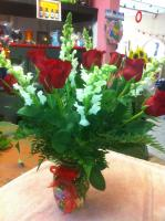 red rosas with snap dragons in a glass vase