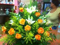 orange roses with white lilys in a baskets
