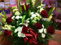 a basket arrangement with red roses, lilys